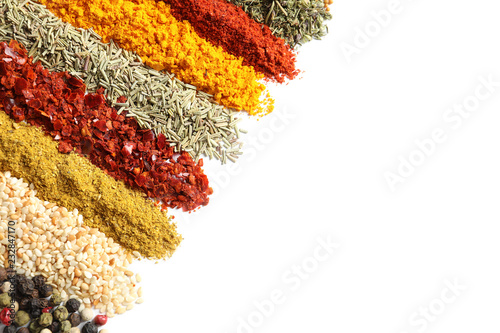 Rows of different aromatic spices on white background, top view with space for text