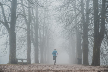 Morning run in foggy winter park. Sport active photo