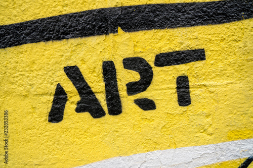 "Fragment of graffiti drawing. Word ""art"" in black on yellow old wall decorated with paint in street art style. - 232853386"