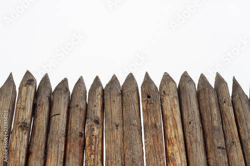 Valokuva  Wooden reliable palisade of strong logs on a white background