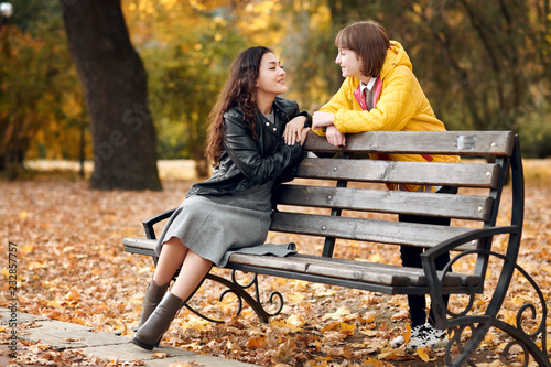 Two girls are in autumn city park Canvas Print