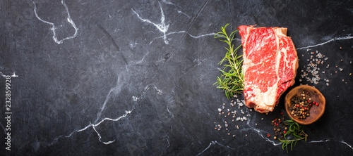 Spoed Foto op Canvas Vlees Raw Fresh Marbled Meat Beef Steak. Herbs and Seasonings on a black marble Background Rosemary Pepper and Salt Ingredients for Cooking Top View Copy space for Text