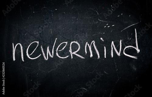 Photo  word nevermind written in white chalk on a school blackboard