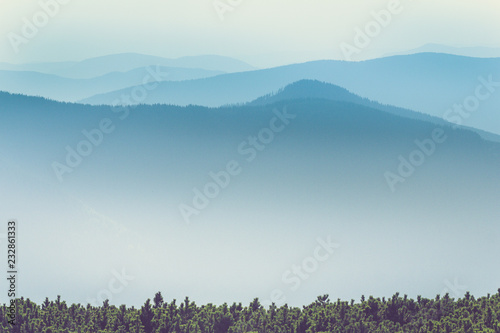 Foto op Aluminium Heuvel Misty mountain hills landscape. View of layers of mountains and haze in the valleys. The effect of color tinting.