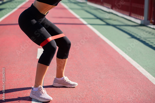 Fotografía  Slender fitness girl doing woman doing squats with rubber resistance band on a bridge
