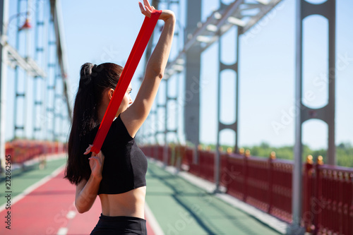 Fotografia Beautiful sporty girl doing training with rubber resistance band on a bridge
