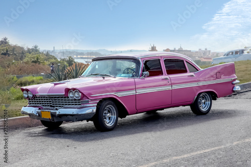 Photographie  Classic vintage / retro american car of  1959 from side proection, settled in front of a village landscape
