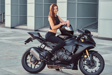 A Sexy Biker Girl Sitting On Her Superbike Outdoors.