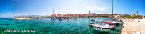 Seaside promenade and harbour in Supetar town on Brac island with palm trees and turquoise clear ocean water, Supetar, Brac, Croatia, Europe