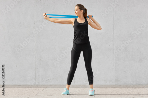 Fotografie, Tablou  Shot of sporty young woman dressed in black clothes, stretches hands with fitness gum, wants to have muscles, has good flexibility, poses against grey background