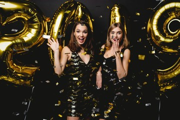 Fototapeta Beautiful Women Celebrating New Year. Happy Gorgeous Girls In Stylish Sexy Party Dresses Holding Gold 2019 Balloons, Having Fun At New Year's Eve Party. Holiday Celebration. High Quality Image