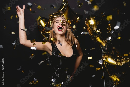 Obraz Cheerful woman with balloons laughing on black background. - fototapety do salonu