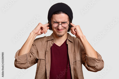 Fotografía  Stressful teenager wears black har and beige shirt, pluggs ears, ignores loud sound coming from noise neighbours, stands against white background