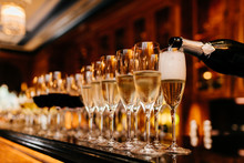 Row Of Glasses Filled With Champagne And Other Beverages, Someone Holds Bottle And Fills In Glasses. Bar Counter. Banquet