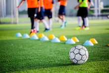 Soccer Ball On Green Artificial Turf With Blurry Of Maker Cones And Player Training.