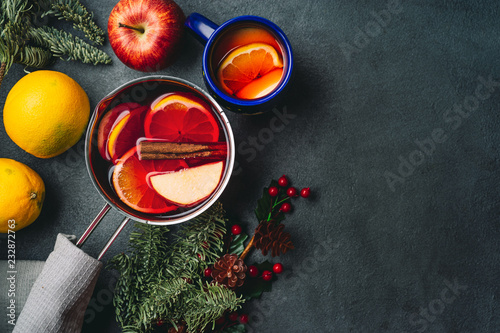 Top view of mulled wine in a pot on dark background
