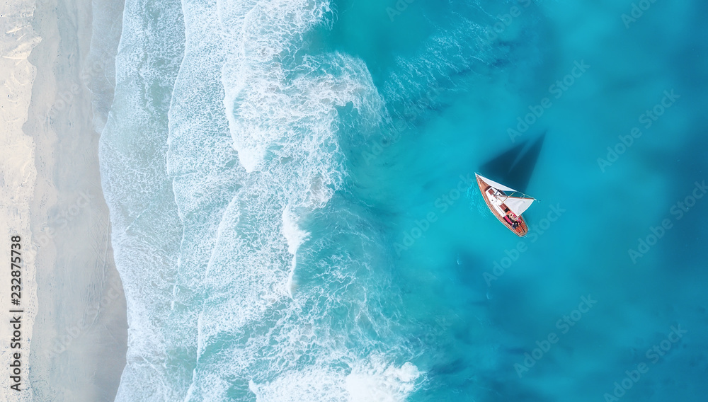 Fototapeta Yacht on the water surface from top view. Turquoise water background from top view. Summer seascape from air. Travel concept and idea