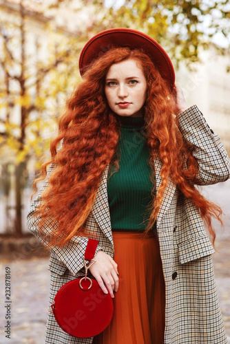Photo  Street fashion portrait of young beautiful redhead woman with freckles, very lon
