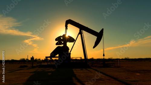 Industrial jack pump platform pumping crude oil over sunset sun