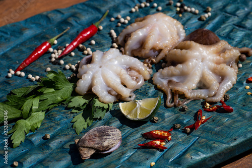 Fresh octopus in a blue plate with parsley and red pepper. On a wooden table.