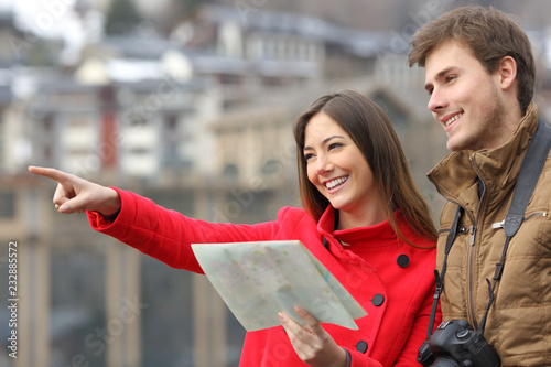 Couple of tourists holding map and pointing away