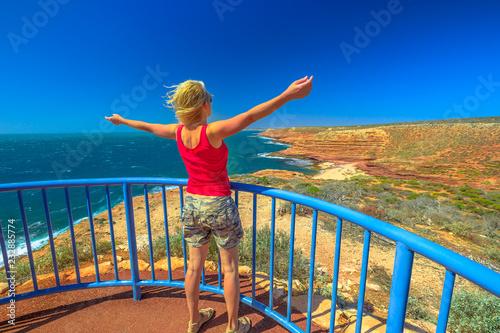 Photo Stands Nice Happy backpacker woman at Eagle Gorge Lookout platform in Kalbarri National Park, Western Australia. Caucasian girl enjoying cliffs of Indian Ocean coastline. Australian Outback. Blue sky in summer.