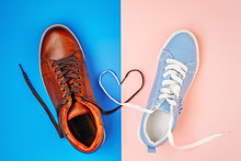 Male And Female Shoes On Blue And Pink Background With Shoelaces In A Shape Of Heart, Top View