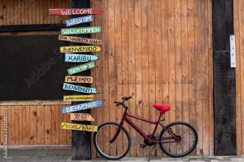 Red Bike Next to a Post with Welcome Signs in Several
