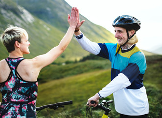 Fototapeta Cyclists giving each other a high five