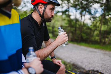Fototapeta Cyclist resting and drinking water in the forest