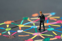 Anti Social Man, Business Connection Or Social Network Concept, Miniature People Businessman Standing On Colorful Pastel Chalk Line Link And Connect Between Multiple Dot Or Tiers On Blackboard