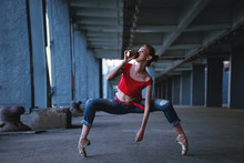 Ballerina Dancing With Cup Of Coffee In Jeans, T-shirt And Pointe. Street Performance. Modern Ballet. Thin Girl Is Drinking From A Paper Glass With A Hot Drink.