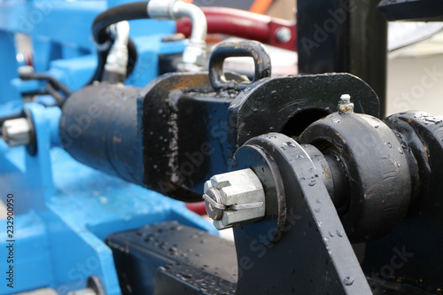 Black hydraulic cylinder on the blue frame  - Buy this stock photo