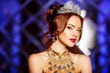Woman Queen Princess In Crown And Lux Dress, Lights Party Background Luxury Girl Long Shiny Healthy Volume Hair Waves Curls. Updo Hairstyle. Salon Fashion Model Luxurious Vintage Interior.