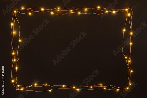 Fototapeta Christmas lights garland border over black background. Flat lay, copy space. obraz