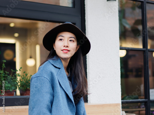 Photo Beautiful young brunette woman in blue coat looking aside with smile expression