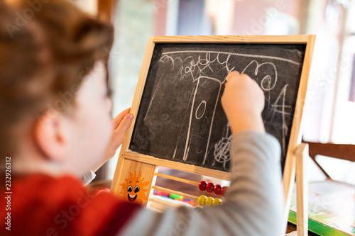 Bambina che disegna sulla lavagna divertendosi Canvas Print