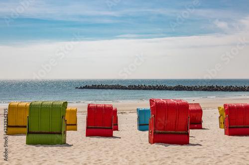 Farbige Strandkörbe am Sandstrand auf einer Insel