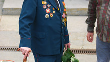 War Veteran Holding Bouquet Of Roses. Winner In The Second World War With Awards And Medals. Veterans Commemorate Great Patriotic War.