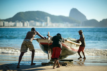 Fishermen Pushing A Traditional Wooden Fishing Boat Into The Sea At Copacabana Beach With The Dramatic Mountain Skyline Of Rio De Janeiro, Brazil