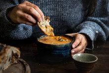 Woman Dipping Bread Into A Pumpkin Soup
