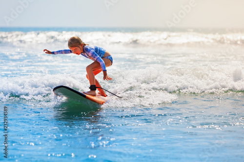 Wallpaper Mural Happy baby girl - young surfer ride on surfboard with fun on sea waves