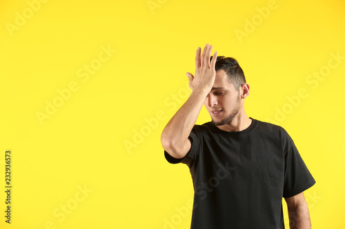 Valokuva  Emotional young man after making mistake on color background