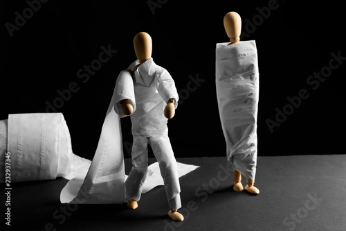 Cuadros en Lienzo Funny wooden mannequins wrapped in toilet paper on table against dark background