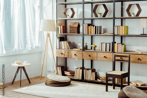 Photo interior of living room with wooden furniture and books