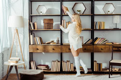 Fotografia  beautiful adult woman taking book from wooden rack