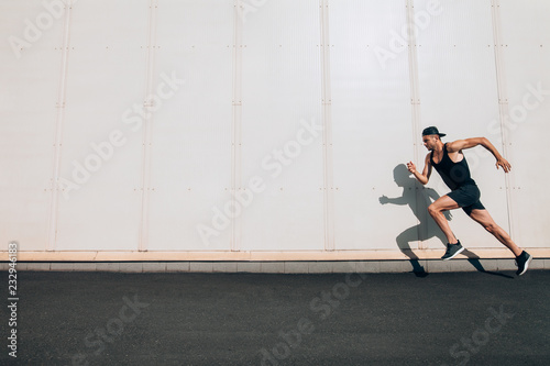 Fotografija Young man runner running along wall with copy space