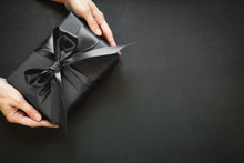 Black Gift Box In Female Hand. Top View. Black Friday. Shopping And Sales.