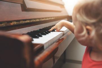 Obraz na Szkle music education - child pushing piano keys