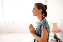 Religion, Faith And People Concept - Close Up Of Woman Meditating At Yoga Studio